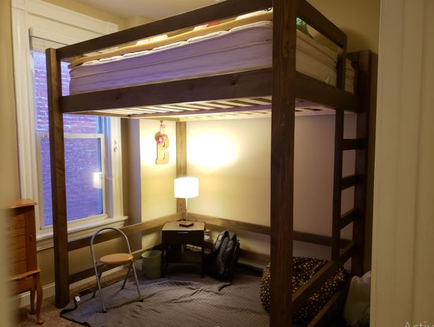 a tall queen loft bed with light and table