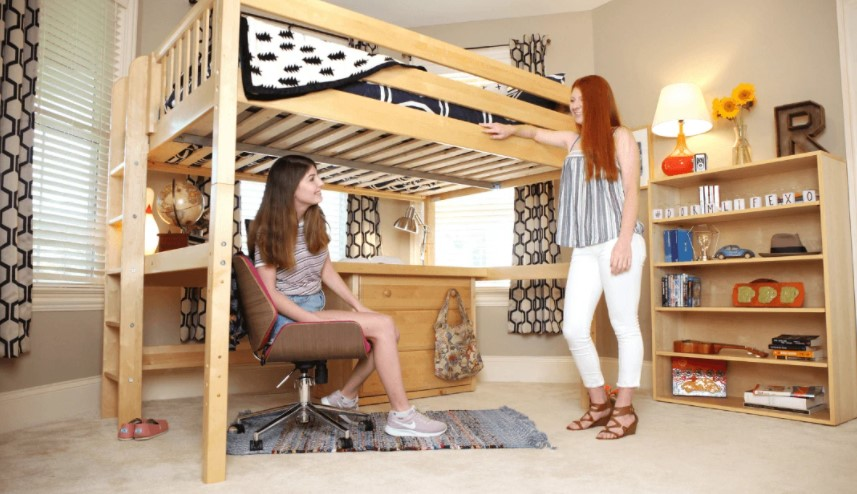 a lady sitting below a queen loft bed with drawers