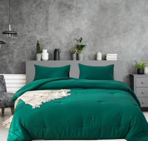 emerald green pillows on a bed and a green duvet cover